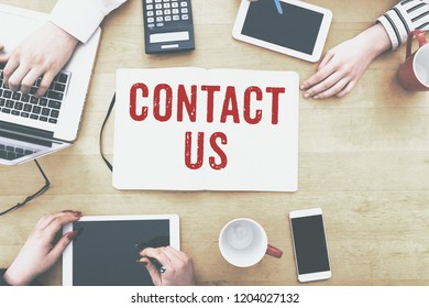 Contact Us message written in light box on office desk flat lay