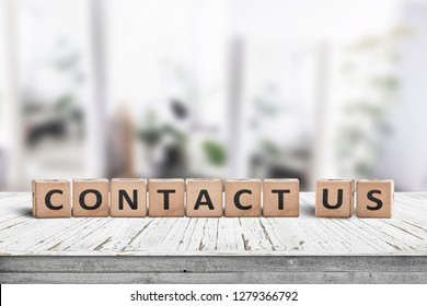 Contact us sign on a wooden desk in a bright living room with green plants