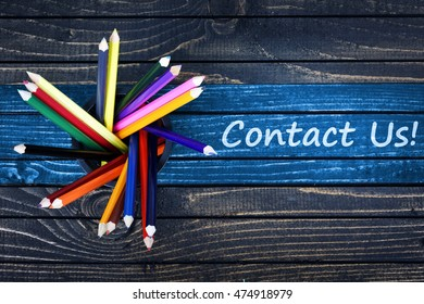 Contact Us text painted and group of pencils on wooden table