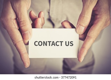 """"""" contact us """" word on card hold by man"""