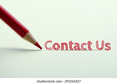 Contact us word is standing on the paper with red pencil aside.