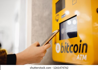 Contactless ATM machine for payment by Bitcoin cryptocurrency. Concept pay mobile phone.