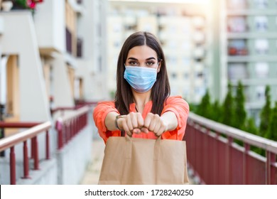 Contactless delivery of goods during Covid 19, coronavirus pandemic. The food delivery courier is holding a large paper bag in her hands. Woman with medical mask delivering food.