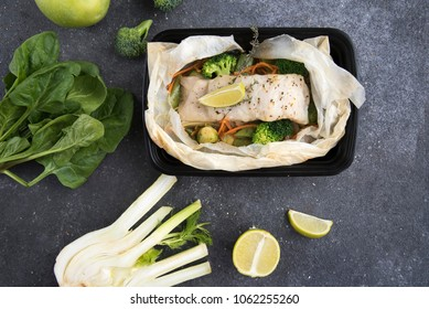 container with baked fish and green vegetables on a dark background. food delivery. healthy food