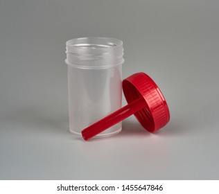 container for biomaterial with spoon on gray background