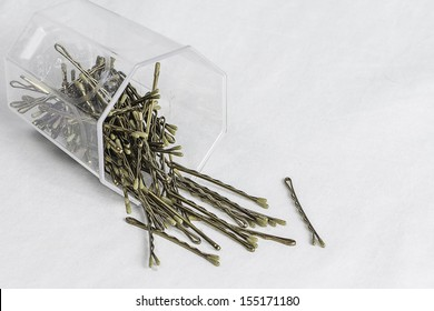 A container of bobby hair pins pouring out.