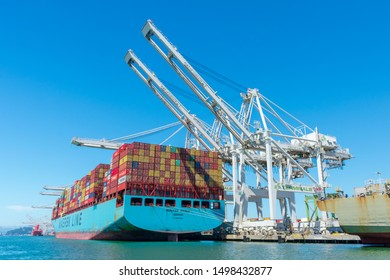 Container cargo cranes unloading container ship Maersk Essex operated by Maersk Line at Oakland International Container Terminal under blue sky - Oakland, California, USA - Circa August, 2019