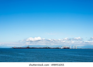 container cargo ships and cranes near an industrial logistic port in horizon,  blue sky and clouds behind.