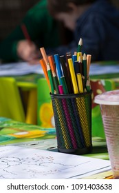 Container and color pencils with drawing at preschool