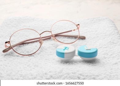 Container with contact lenses and glasses on towel