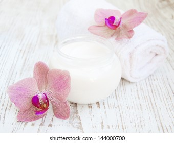 container of cosmetic moisturizing cream with pink orchids and towel