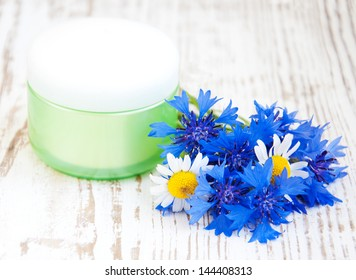 container with cream  and cornflowers on white wooden background