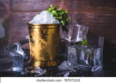 A container with ice stands among ice cubes and mint.