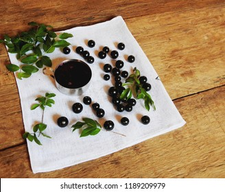 container with jabuticaba jelly fruit branches and leaves on white cloth on rustic wooden table top view