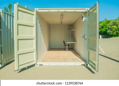 Container on a construction site, exterior. Mobile building. Cargo container apartment. Prefabricated mobile cargo containers with a window and door used for housing, home container, rooms.
