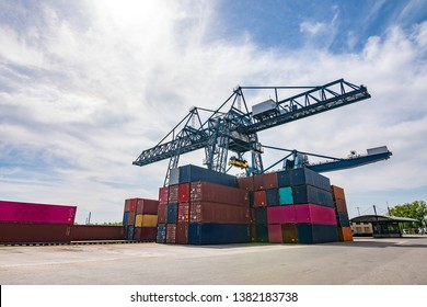 The container port without any people/worker on a sunny summer day with some clouds.