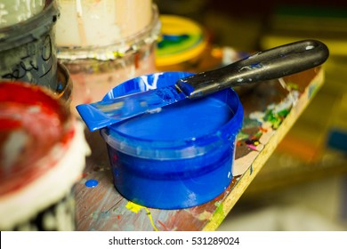 Container and putty knife with different paints for the press