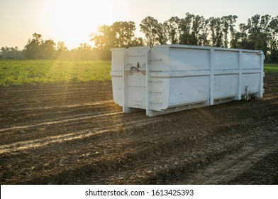 Container for roll-off skip loader at potatoes field at sunset. Potatoes harvest season at Vegas del Guadiana, Spain