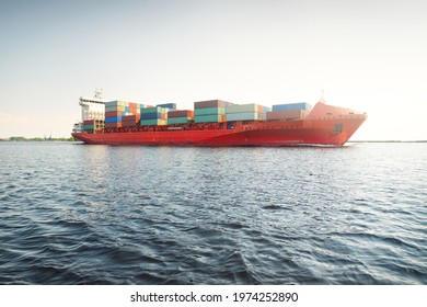 Container ship (168 meters length) leaving port terminal at sunset. Baltic sea. Freight transportation, logistics, global communications, worldwide shipping, economy, business, industry