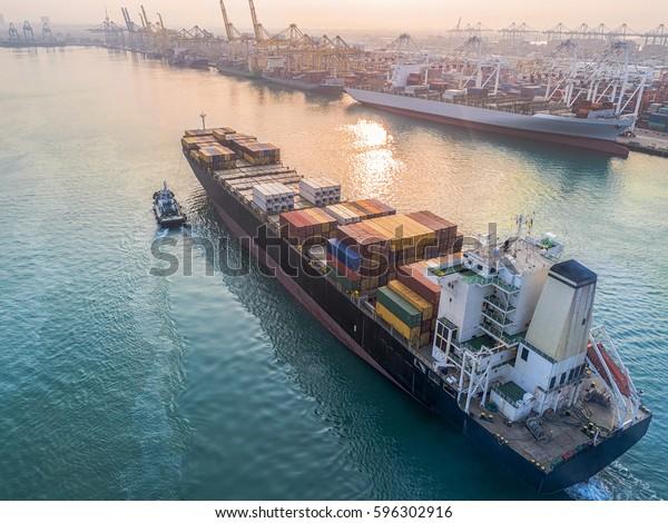 コンテナ船商船が港湾水路に到着するのを期待し、タグ船が国際港湾物流サービスの入り口の安全入り口を手伝う