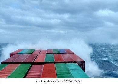 A container ship during stormy weather, water spraying on deck and containers