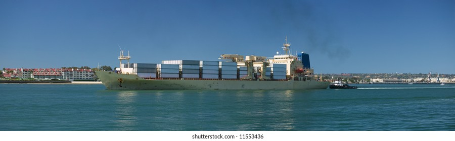 Container ship entering port with a tug assisting