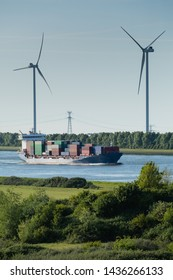 Container ship entering the seaport of Rotterdam with windmills in the background.
