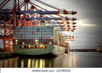 Container ship in the harbor of Hamburg, night shot. Cloudy sky.
