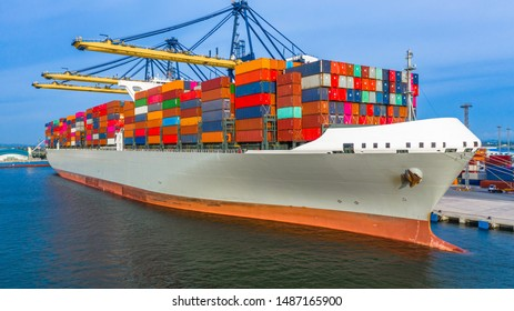 Container ship loading and unloading in deep sea port, Aerial top view of business logistic import and  export freight  transportation by container ship in open sea.