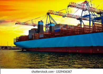 Container ship in port under loading at sunrise.