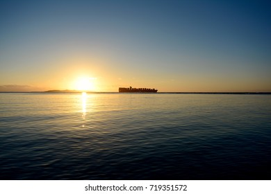 A container ship sailing across the horizon at sunrise