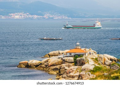 Container ship sailing near Punta Cabalo lighthouse in Arousa Island