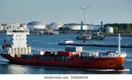 Container ship at the seaport of Rotterdam with chemical and oil industry in the background.