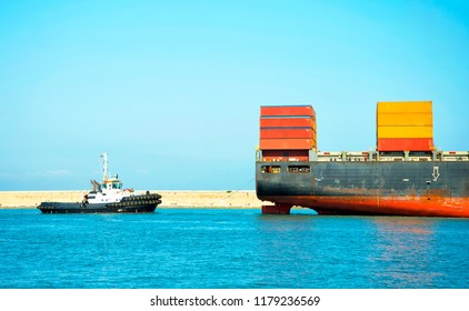 Container ship and tugboat entering the port
