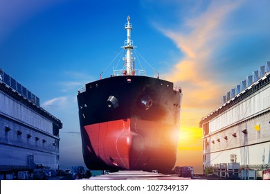 container ship under repair at floating dry dock in shipyard on sunset background