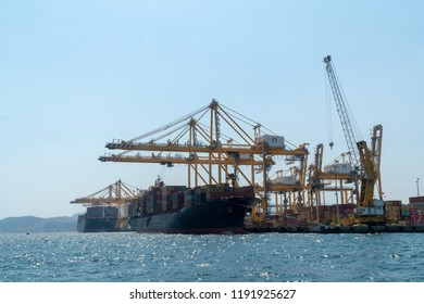 Container ship which is full of containers docked at port. Cranes are loading containers to cargo ship.