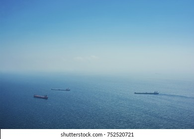 Container ships in the distance on a clear blue day.