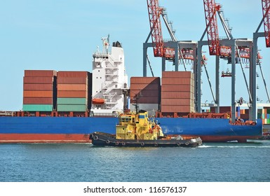 Container stack, ship and tugboat under crane bridge