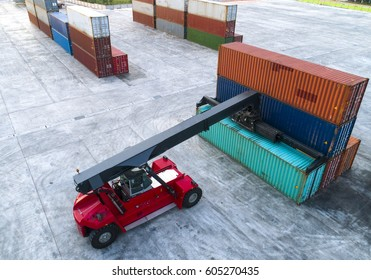 container stacker forklift working on lifting unit of container in yard in aerial view