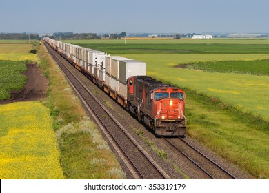 Container train on one of two tracks crossing colorful prairie