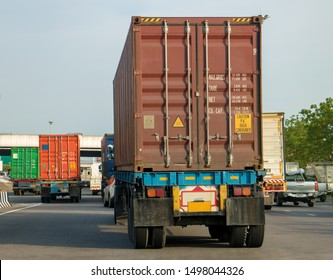 Container transport by truck on the highway. Trucks transporting color containers by road, rear view.