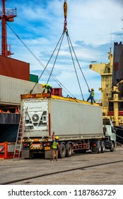 container unit being lift loading by the ship crane from the trailer to accommodation on bay storage, stevedore labor works in charge, the services of logistics and transport shipment to worldwide