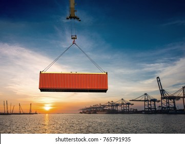 Container unit being lifting loading by the gantry crane of the port to transfer from the storage yard to the bay of the ship, with the sunset and port congestion in background