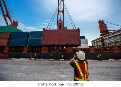 container unit loading onto the bay of ship from terminal yard by the ship crane, accommodate under loading master command with gang of stevedore