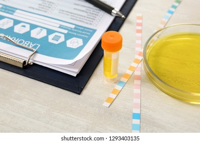 Container with urine sample for analysis, litmus paper and medical report on table in laboratory