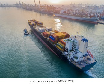 container vessel commercial ship arrival to the international port for logistics worldwide services transferring shipment cargo containers, under handle of tugs boat assist safety , in aerial view