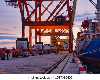 The container vessel during discharging at an industrial port on twilight time.
