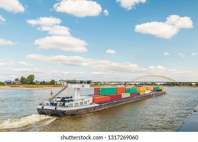 Container vessel passing the city of Nijmegen on the Dutch river Waal in Gelderland
