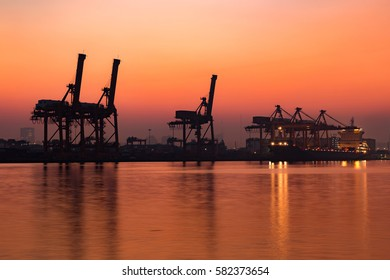 Container-handling gantry cranes silhouetted against setting sun foggy morning in Bangkok Thailand.