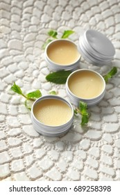 Containers with lemon balm salve and leaves on textured surface